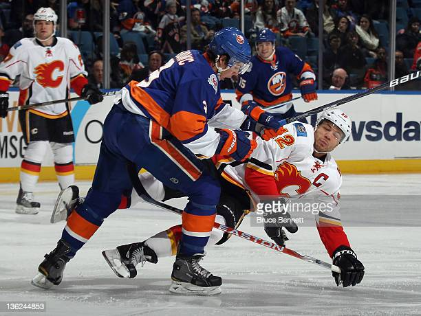 Travis Hamonic of the New York Islanders steps into Jarome Iginla of the Calgary Flames at the Nassau Veterans Memorial Coliseum on December 29 2011...