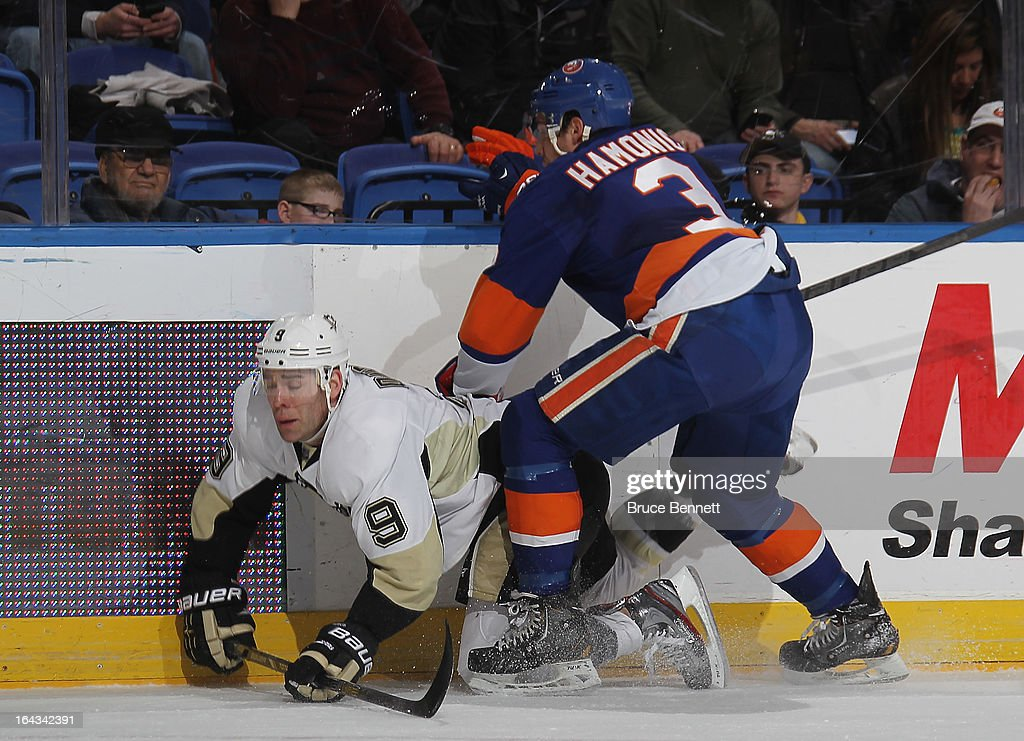 Travis Hamonic #3 of the New York Islanders trips up Pascal Dupuis #9 of the Pittsburgh Penguins during the first period at Nassau Veterans Memorial Coliseum on March 22, 2013 in Uniondale, New York.