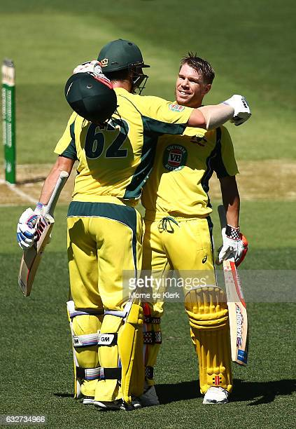 Travis Head of Australia congratulates teammate David Warner after he reached 100 runs during game five of the One Day International series between...