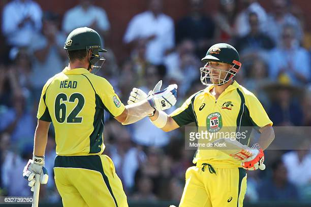 Travis Head of Australia congratulates teammate David Warner of Australia after he reached 150 runs during game five of the One Day International...