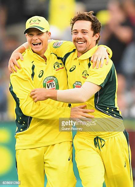 Travis Head of Australia is congratulated by Steve Smith after getting the wicket of Martin Guptill of New Zealand during game three of the One Day...