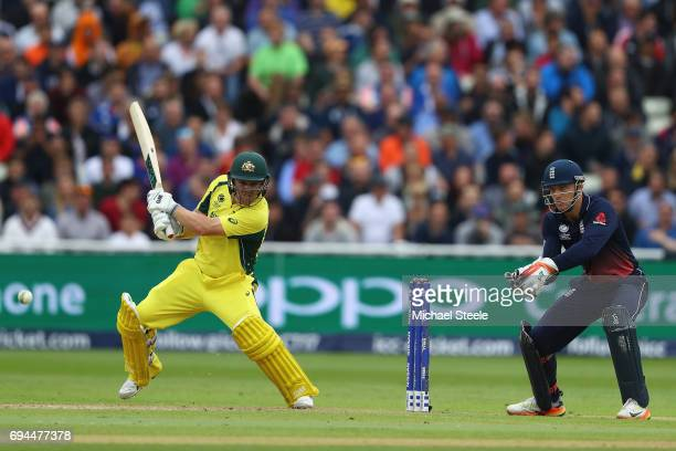 Travis Head of Australia plays to the offside as wicketkeeper Jos Buttler of England looks on during the ICC Champions Trophy match between England...