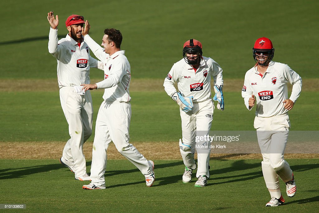 Travis Head of the Redbacks celebrates with teammates after he got the wicket of Matthew Wade of the VIC Bushrangers during day one of the Sheffield Shield match between South Australia and Victoria at Adelaide Oval on February 14, 2016 in Adelaide, Australia.