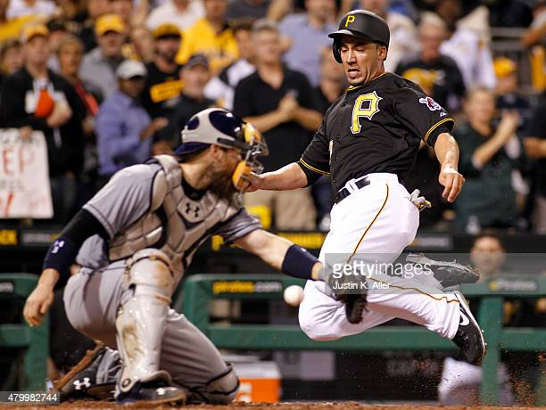 Travis Ishikawa of the Pittsburgh Pirates slides in safe against catcher Derek Norris of the San Diego Padres on a RBI single in the eighth inning...