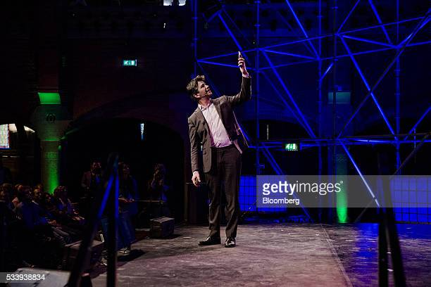 Travis Kalanick billionaire and chief executive officer of Uber Technologies Inc holds up a mobile device whilst speaking during the opening of...