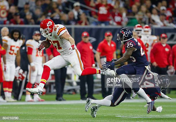 Travis Kelce of the Kansas City Chiefs carries the ball against Kareem Jackson and Johnathan Joseph of the Houston Texans in the fourth quarter...
