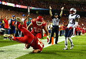Travis Kelce of the Kansas City Chiefs scores a touchdown as Patrick Chung of the New England Patriots defends during the second half at Arrowhead...