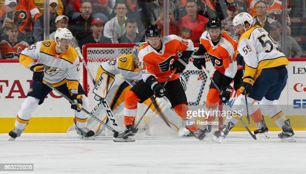 Travis Konecny and Sean Couturier of the Philadelphia Flyers battle for the airborn puck in front of goaltender Pekka Rinne of the Nashville...
