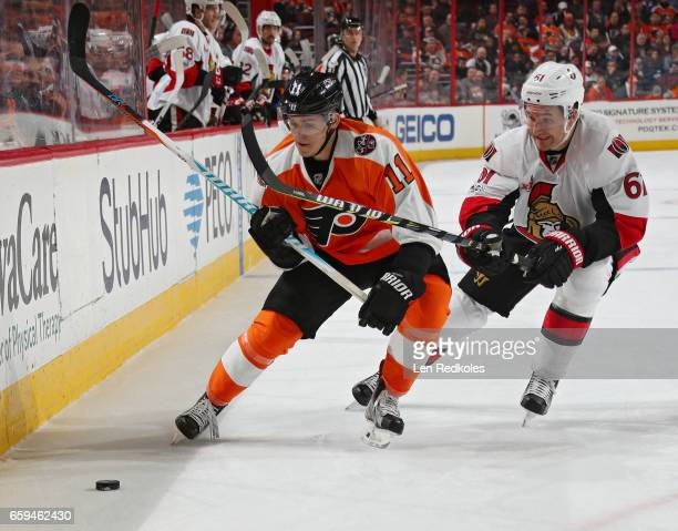 Travis Konecny of the Philadelphia Flyers battles along the boards for the loose puck with Mark Stone of the Ottawa Senators on March 28 2017 at the...