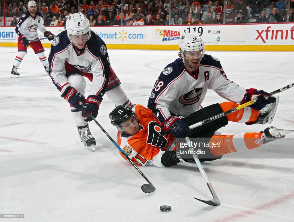 Travis Konecny #11 of the Philadelphia Flyers falls to the ice while battling in the corner for the loose puck with Zach Werenski #8 and Boone Jenner #38 of the Columbus Blue Jackets on March 13, 2017 at the Wells Fargo Center in Philadelphia, Pennsylvania. The Blue Jackets went on to defeat the Flyers 5-3.