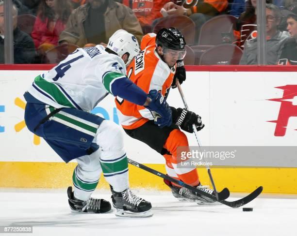 Travis Konecny of the Philadelphia Flyers fends off Erik Gudbranson of the Vancouver Canucks on November 21 2017 at the Wells Fargo Center in...