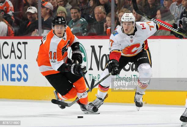 Travis Konecny of the Philadelphia Flyers skates after the loose puck against Mark Jankowski of the Calgary Flames on November 18 2017 at the Wells...