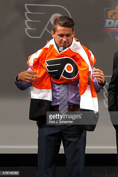 Travis Konecny puts on the Philadelphia Flyers jersey after being selected 24th overall by the Philadelphia Flyers during Round One of the 2015 NHL...