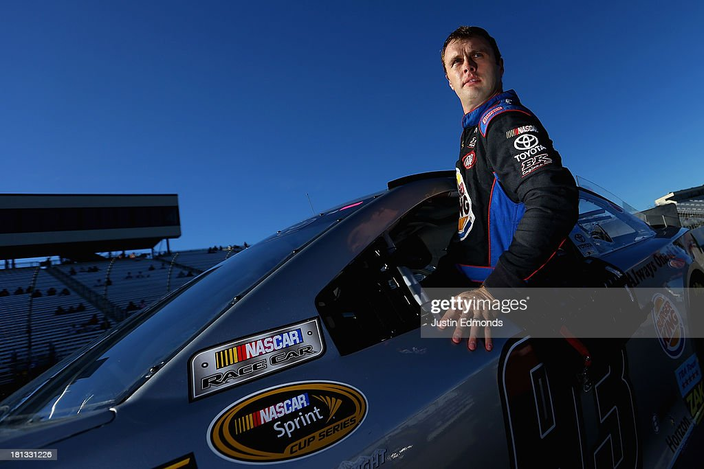 Travis Kvapil, driver of the #93 Burger King / Dr. Pepper Toyota, climbs from his car after qualifying for the NASCAR Sprint Cup Series Sylvania 300 at New Hampshire Motor Speedway on September 20, 2013 in Loudon, New Hampshire.
