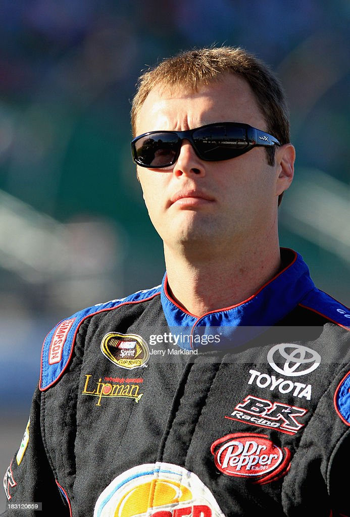 Travis Kvapil, driver of the #93 Burger King / Dr Pepper Toyota, stands on the grid during qualifying for the NASCAR Sprint Cup Series 13th Annual Hollywood Casino 400 at Kansas Speedway on October 4, 2013 in Kansas City, Kansas.