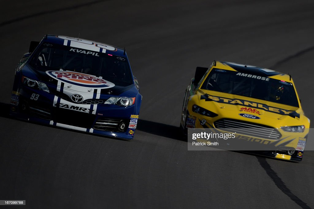 Travis Kvapil, driver of the #93 Burger King/Dr. Pepper Toyota, and Marcos Ambrose, driver of the #9 Stanley Ford, practice for the NASCAR Sprint Cup Series STP 400 at Kansas Speedway on April 20, 2013 in Kansas City, Kansas.