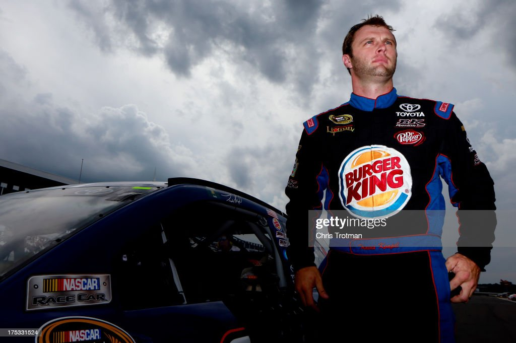 Travis Kvapil, driver of the #93 Burger King/Dr. Pepper Toyota, gets out of his car after qualifying for the NASCAR Sprint Cup Series GoBowling.com 400 at Pocono Raceway on August 2, 2013 in Long Pond, Pennsylvania.