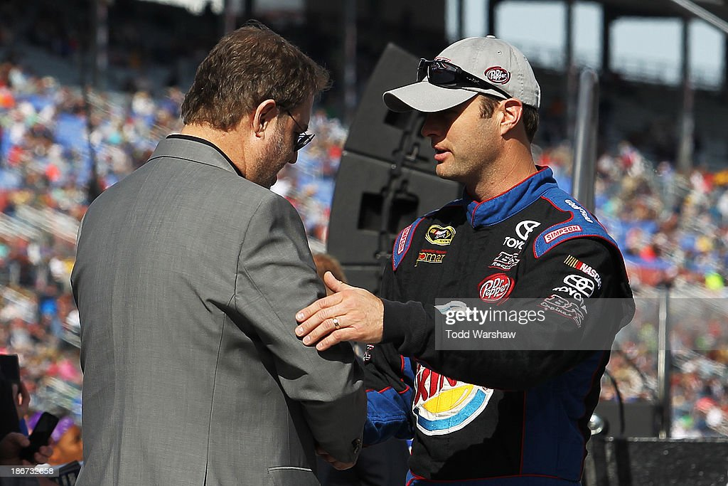 Travis Kvapil, driver of the #93 Dr. Pepper / Burger King Toyota, greets Texas Motor Speedway president Eddie Gossage during the NASCAR Sprint Cup Series AAA Texas 500 at Texas Motor Speedway on November 3, 2013 in Fort Worth, Texas.
