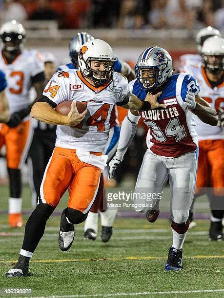 Travis Lulay of the BC Lions protects the ball from Kyries Hebert of the Montreal Alouettes during the CFL game at Percival Molson Stadium on...