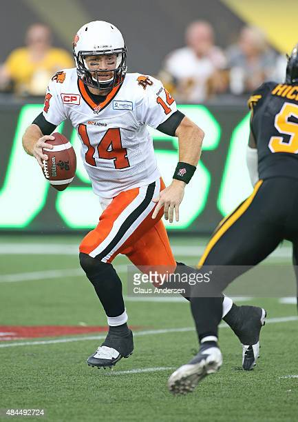 Travis Lulay of the BC Lions rolls out to make a play against the Hamilton TigerCats during a CFL football game at Tim Hortons Field on August 15...
