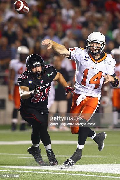 Travis Lulay of the BC Lions throws a pass with pressure coming from Justin Capicciotti of the Ottawa Redblacks during a CFL game at TD Place Stadium...
