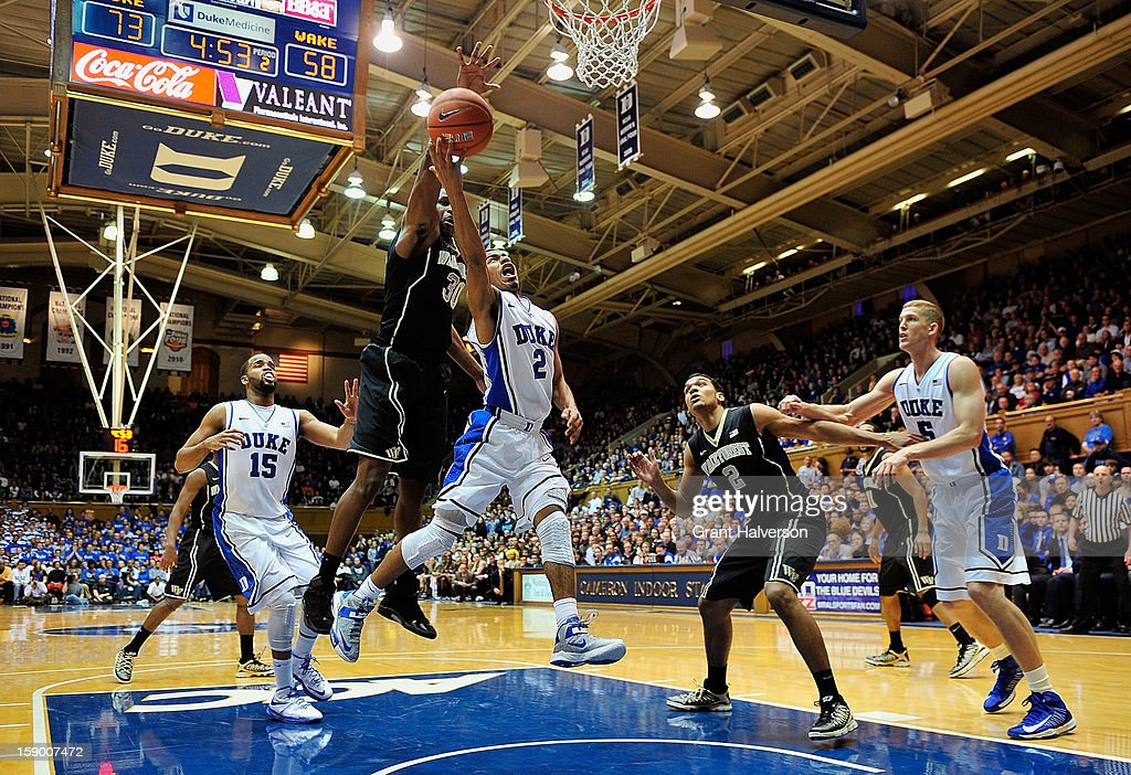 Travis McKie #30 of the Wake Forest Demon Deacons blocks a shot by Quinn Cook #2 of the Duke Blue Devils during play at Cameron Indoor Stadium on January 5, 2013 in Durham, North Carolina. Duke won 80-62.