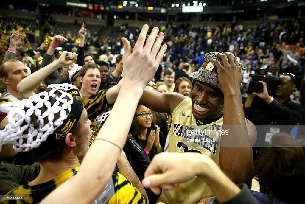 Travis McKie of the Wake Forest Demon Deacons celebrates with students after defeating the Duke Blue Devils 8272 at Joel Coliseum on March 5 2014 in...