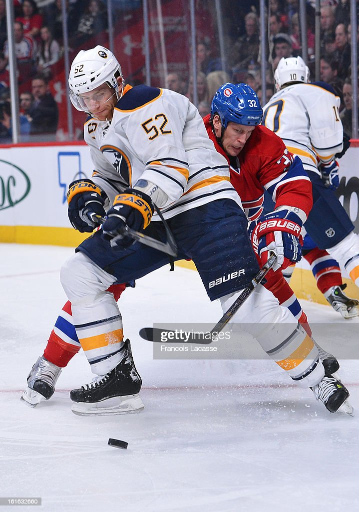 Travis Moen #32 of the Montreal Canadiens and Alexander Sulzer #52 of the Buffalo Sabres battles for the puck during the NHL game on February 2, 2013 at the Bell Centre in Montreal, Quebec, Canada.