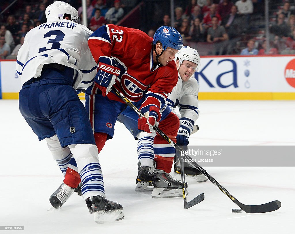 <a gi-track='captionPersonalityLinkClicked' href=/galleries/search?phrase=Travis+Moen&family=editorial&specificpeople=208110 ng-click='$event.stopPropagation()'>Travis Moen</a> #32 of the Montreal Canadiens controls the puck while being challenged by <a gi-track='captionPersonalityLinkClicked' href=/galleries/search?phrase=Dion+Phaneuf&family=editorial&specificpeople=545455 ng-click='$event.stopPropagation()'>Dion Phaneuf</a> #3 and <a gi-track='captionPersonalityLinkClicked' href=/galleries/search?phrase=Cody+Franson&family=editorial&specificpeople=2125769 ng-click='$event.stopPropagation()'>Cody Franson</a> #4 of the Toronto Maple Leafs during the NHL game on October 1, 2013 at the Bell Centre in Montreal, Quebec, Canada.