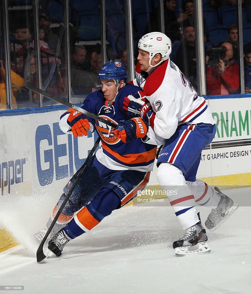 Travis Moen #32 of the Montreal Canadiens hits Travis Hamonic #3 of the New York Islanders into the boards at the Nassau Veterans Memorial Coliseum on March 5, 2013 in Uniondale, New York.