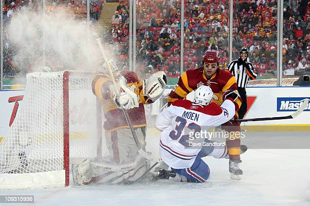 Travis Moen of the Montreal Canadiens slides into the crease area as goaltender Miikka Kiprusoff and Mark Girodano of the Calgary Flames defend the...