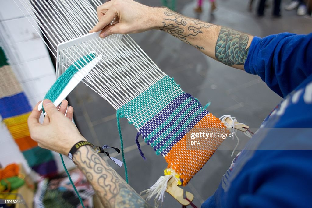 Travis of the label Mavi is weaving a blanket for refugees staying at Oranienplatz Square in Berlin during the fashion fair 'Bread & Butter' at the former airport Tempelhof in Berlin, on January 15, 2013. The shows of the autumn/winter 2013/2014 collections are running from 15 to 17 January 2013. AFP PHOTO / Jörg Carstensen /GERMANY OUT