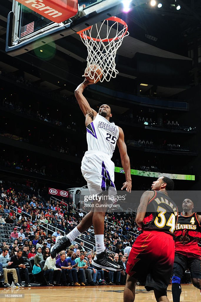 Travis Outlaw #25 of the Sacramento Kings rises for a dunk against Devin Harris #34 of the Atlanta Hawks on February 22, 2013 at Philips Arena in Atlanta, Georgia.