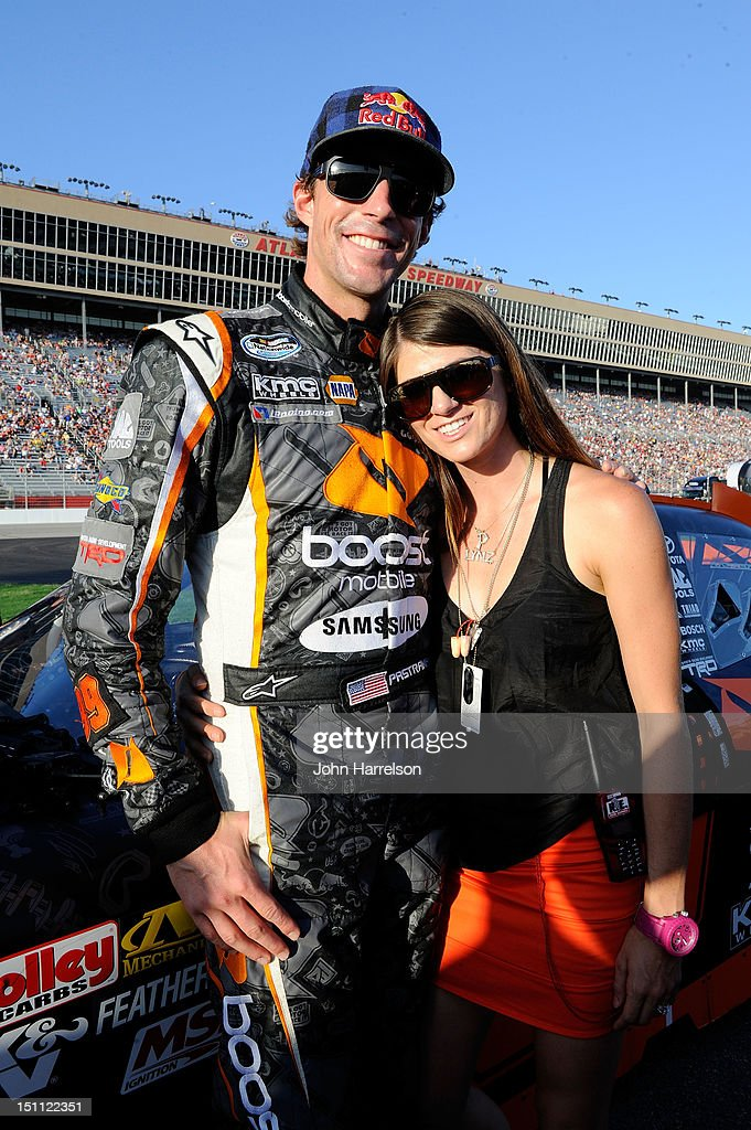 Travis Pastrana, driver of the #99 Boost Mobile Toyota, and his wife Lyn-Z pose on the grid prior to the start of the NASCAR Nationwide Series NRA American Warrior 300 at Atlanta Motor Speedway on September 1, 2012 in Hampton, Georgia.