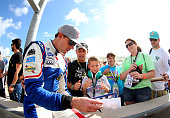 Travis Pastrana driver of the Nitro City Ford signs autographs during qualifying for the NASCAR Nationwide Series Ford EcoBoost 300 at HomesteadMiami...