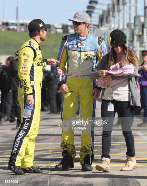 Travis Pastrana driver of the Roush Fenway Racing Ford wife Lynz and daughter Addy talk with Brian Vickers driver of the Dollar General Toyota on the...