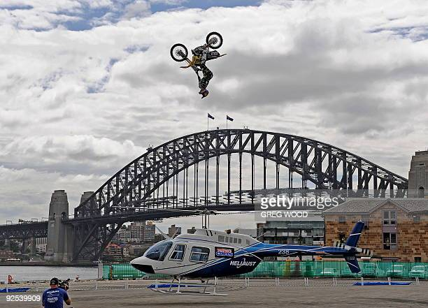 Travis Pastrana of the US performs an FMX back flip on his dirt bike over a hovering 43foot helicopter in front of the Sydney Harbour Bridge on...