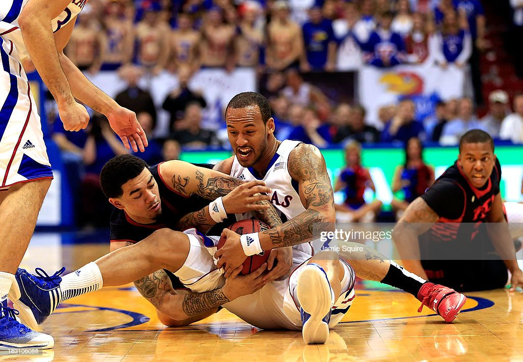 Travis Releford #24 of the Kansas Jayhawks battles Josh Gray #5 of the Texas Tech Red Raiders for a loose ball during the game at Allen Fieldhouse on March 4, 2013 in Lawrence, Kansas.