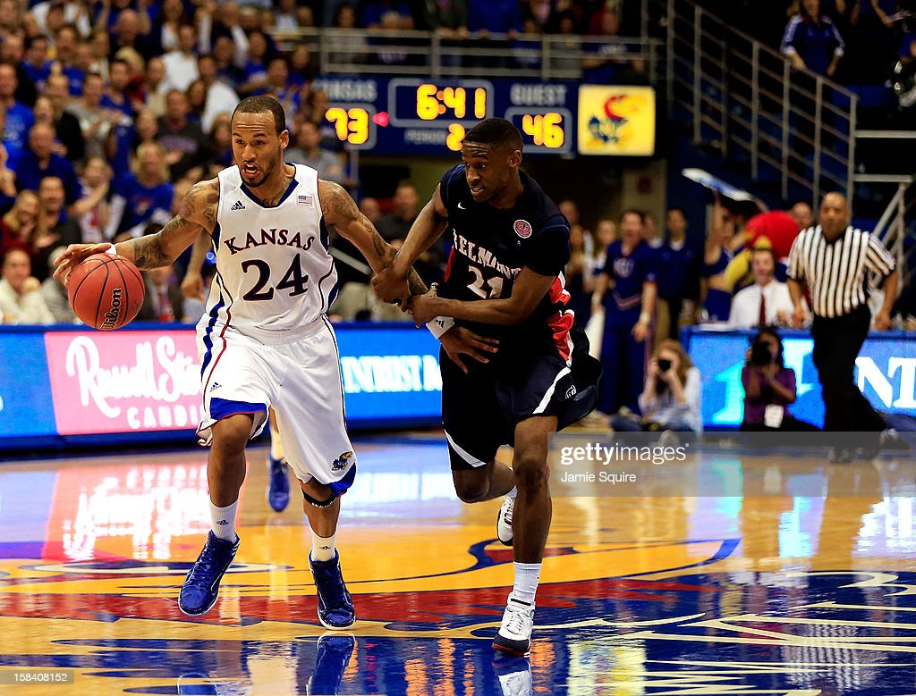 Travis Releford #24 of the Kansas Jayhawks drives downcourt on a fast break as Ian Clark #21 of the Belmont Bruins defends during the game at Allen Fieldhouse on December 15, 2012 in Lawrence, Kansas.