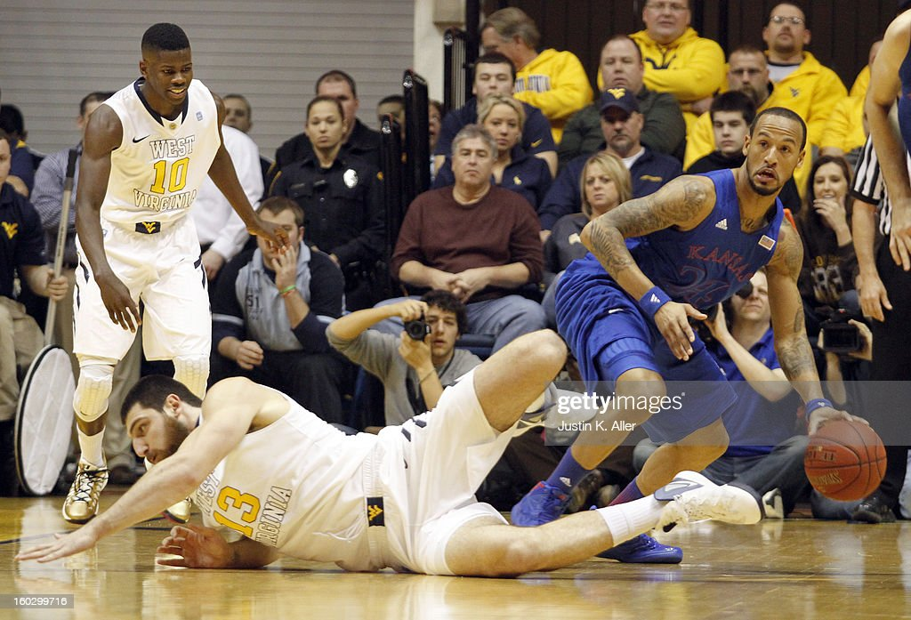 Travis Releford #24 of the Kansas Jayhawks handles the ball behind Deniz Kilicli #13 of the West Virginia Mountaineers at the WVU Coliseum on January 28, 2013 in Morgantown, West Virginia.