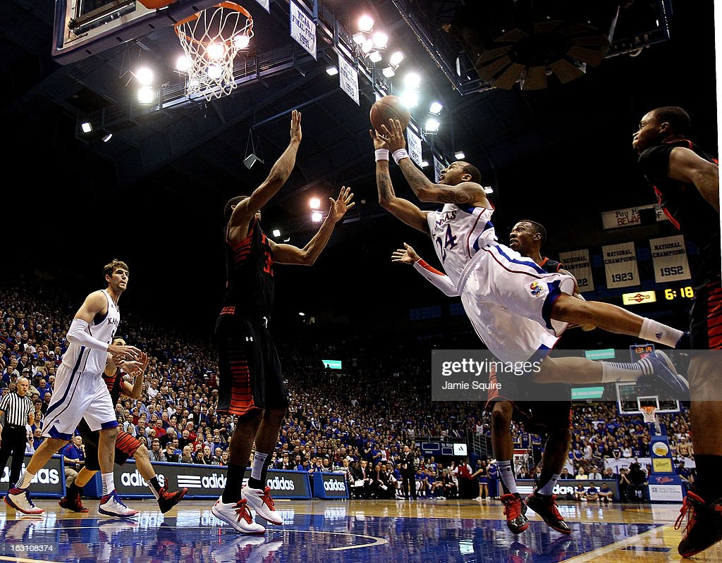 Travis Releford #24 of the Kansas Jayhawks is fouled as he drives during the game against the Texas Tech Red Raiders at Allen Fieldhouse on March 4, 2013 in Lawrence, Kansas.