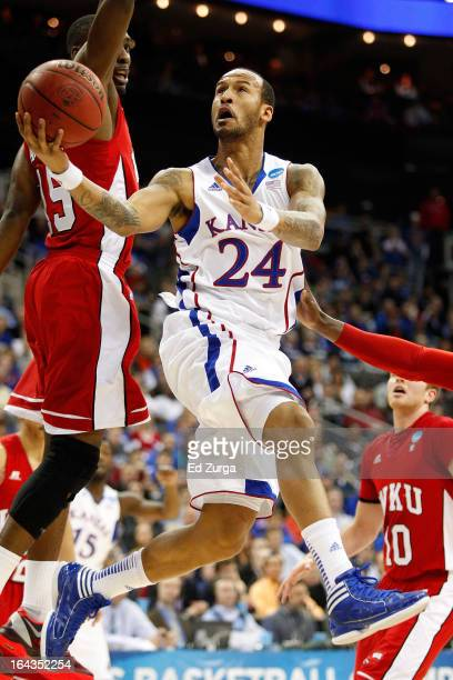 Travis Releford of the Kansas Jayhawks shoots against O'Karo Akamune and Caden Dickerson of the Western Kentucky Hilltoppers in the first half during...