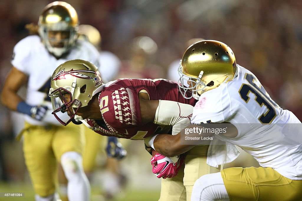 Travis Rudolph #15 of the Florida State Seminoles is stopped by Cole Luke #36 of the Notre Dame Fighting Irish during their game at Doak Campbell Stadium on October 18, 2014 in Tallahassee, Florida.