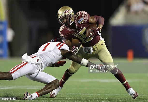 Travis Rudolph of the Florida State Seminoles is tackled by Tony Bridges of the Mississippi Rebels in the second half during the Camping World...
