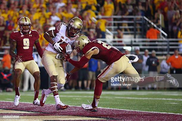 Travis Rudolph of the Florida State Seminoles scores a touchdown with pressure from Justin Simmons of the Boston College Eagles during the first half...
