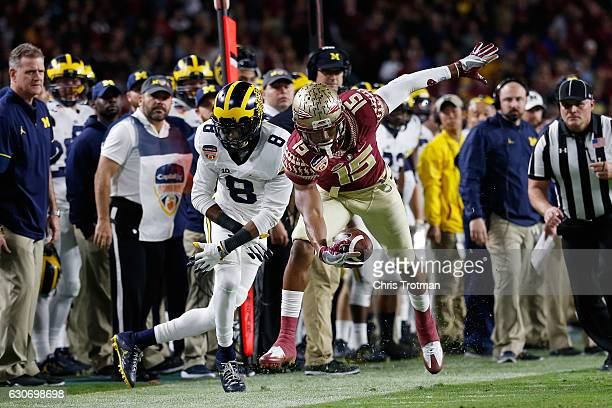 Travis Rudolph of the Florida State Seminoles tries to avoid the tackle of Channing Stribling of the Michigan Wolverines in the first half during the...