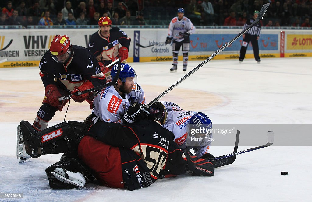 Travis Scott of Hannover blocks the shot of Richard Rochefort of Augsburg during the DEL play off final match between Hannover Scorpions and...