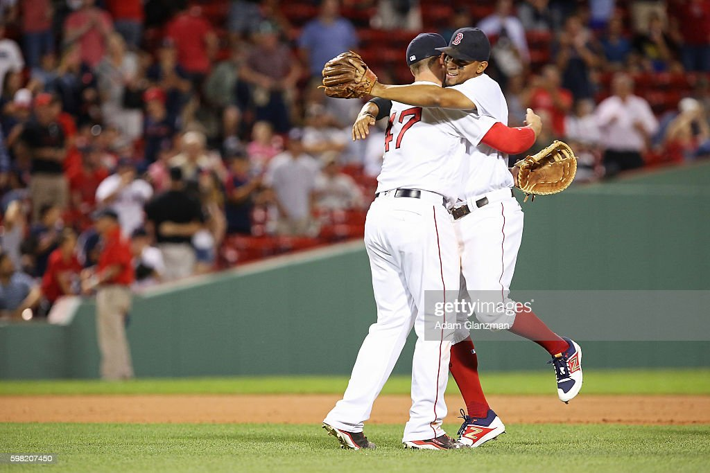 Travis Shaw embraces Xander Bogaerts of Boston Red Sox after their victory over the Tampa Bay Rays at Fenway Park on August 29 2016 in Boston...