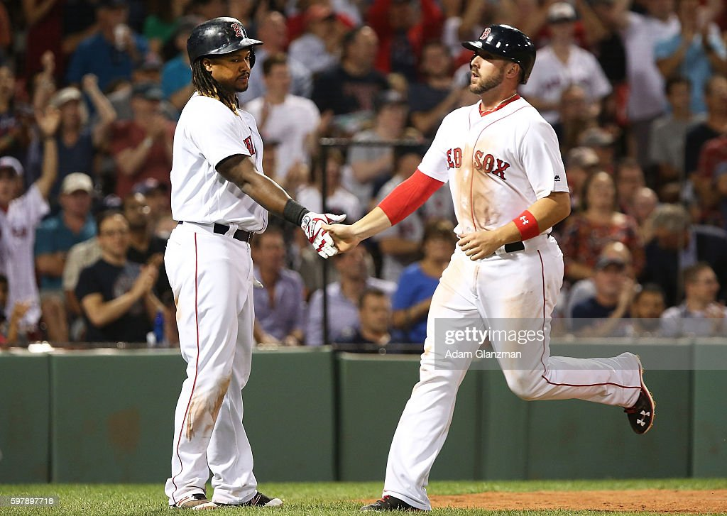 Travis Shaw high fives Hanley Ramirez of the Boston Red Sox after scoring in the seventh inning during a game against the Tampa Bay Rays at Fenway...