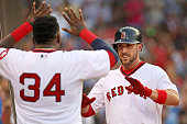Travis Shaw of the Boston Red Sox high fives David Ortiz of the Boston Red Sox after hitting a solo home run in the second inning during the game...
